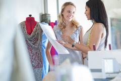 Dressmaker fitting client in studio - stock photo