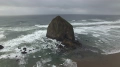 Flyover Haystack Rock on a Stormy Day - stock footage