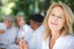 Older woman having wine outdoors - stock photo