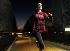 Woman running on pedestrian bridge - stock photo