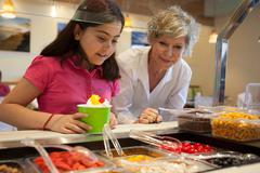 Girl putting toppings on frozen yogurt - stock photo