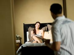 Man greeting girlfriend in bedroom Stock Photos