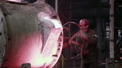 Worker in foundry controlling iron smelting in furnaces Stock Footage