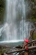 Woman with umbrella admiring waterfall - stock photo