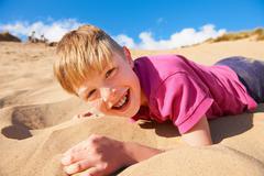 Blonde haired boy lying on beach Stock Photos
