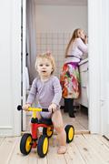 Toddler girl playing on tricycle, mother in background Stock Photos