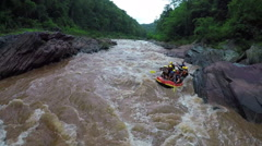 Aerial - Whitewater rafting boat follow shot down river in Thailand. Stock Footage