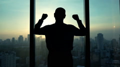 Successful businessman raising arms, power symbol above city, super slow motion, Stock Footage
