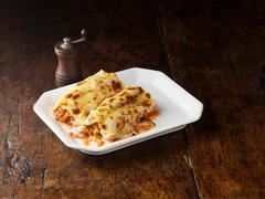Beef Cannelloni on white rectangular plate with wooden pepper grinder Stock Photos