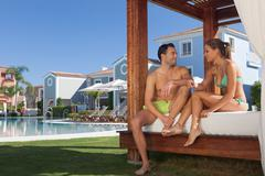 Young couple relaxing on sunlounger at holiday resort Stock Photos