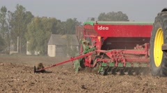 Farmer on farmland with tractor and sower sow cereal crops. Closeup 4K Stock Footage