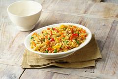 Savoury rice with, peas, red and yellow peppers, carrots and mushrooms in white Stock Photos