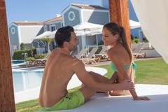 Young couple sitting on sunlounger at holiday resort - stock photo