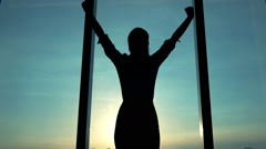 Successful businesswoman raising arms, power symbol above city, super slow motio Stock Footage