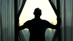 Young man unveil curtains and admire cityscape view, slow motion Stock Footage