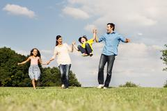 Family with two children, parents swinging boy Stock Photos
