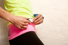 Young woman using stopwatch - stock photo
