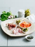 Selection of cured meats and pickles - stock photo