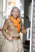Senior woman in leather jacket and scarf opening door Stock Photos