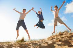 Boys and teenage girl jumping on beach Stock Photos