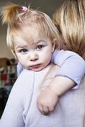 Mother holding toddler daughter over shoulder Stock Photos