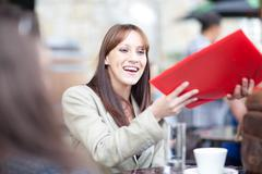 Young woman holding menu in cafe Stock Photos