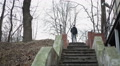 Young man wasting youth while drinking alcohol, wandering in abandoned park Footage