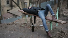 Drunk young guy lying on bench, alcohol abuse problem, hangover after party - stock footage