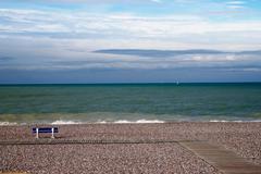 Empty bench on shingle beach Stock Photos