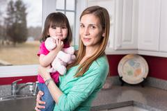 Portrait of mother holding toddler daughter in kitchen - stock photo