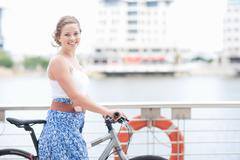 One young woman with her push bike - stock photo