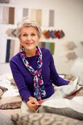 Senior woman choosing textile swatches Stock Photos