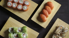 Food, sushi rolls: Male and female hands take sushi sets. Top view - stock footage