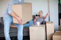 Young woman moving house on sofa directing man with box Stock Photos