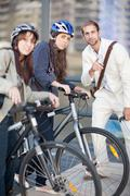 Young women with bicycles asking young man for directions Stock Photos