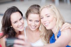 Three young women taking photos and showing them to each other - stock photo