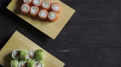 Food, sushi rolls: Male and female hands put on a table sushi sets. Top view - stock footage