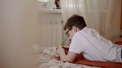 Boy in Glasses Watching Videos on a Tablet Lying on the Bed Stock Footage