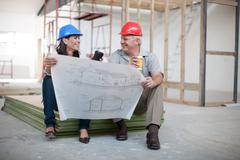 Male and female construction workers sitting down holding coffee and a blueprint Stock Photos