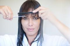 Mid adult woman cutting her own fringe - stock photo