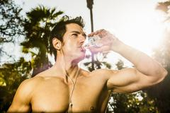 Young man exercising in forest drinking mineral water - stock photo