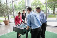 Businesspeople playing table football in lobby Stock Photos