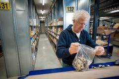Male warehouse worker selecting item from conveyor belt - stock photo