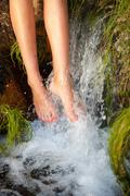 Young woman bathing feet under waterfall Stock Photos