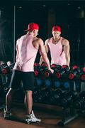 Muscular man out in gym standing near dumbbells,  a pink shirt and red baseball Stock Photos
