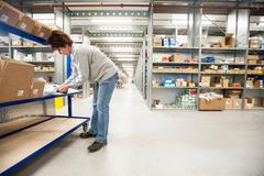 Female warehouse worker checking orders on delivery trolley - stock photo