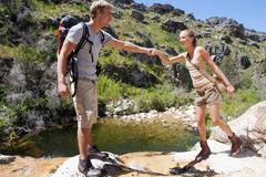 Young hiker assisting woman over rocks Stock Photos