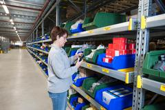Female warehouse worker selecting item from shelving - stock photo