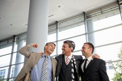 Three businessmen smiling and celebrating - stock photo