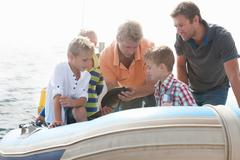 Small group of young men and young boys sea fishing in dinghy Stock Photos